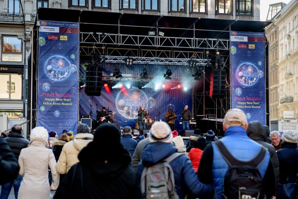 Mehrere Musiker singen auf einer Bühne. Im Vordergrund stehen unzählige Menschen und beobachten die Aufführung.
