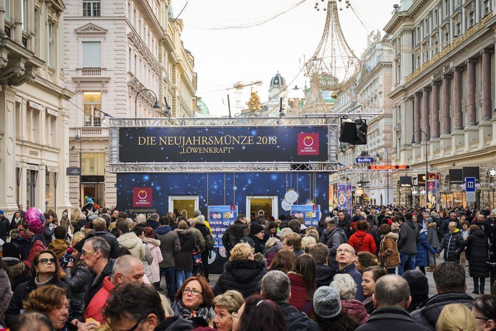 Unzählige Menschen gehen bei Tageslicht in der Innenstadt spazieren. Im Hintergrund eine Bühne mit Logo der Münze Österreich