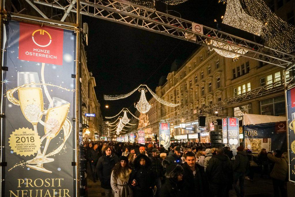 Der Graben bei Nacht mit einem Gerüstturm. Darauf zu sehen eine Werbung der Münze Österreich